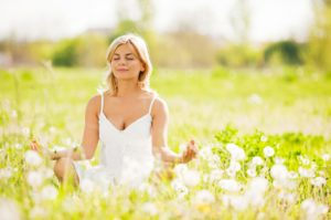 Young woman meditating in the mature.